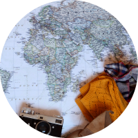 A map with a camera, sweater and scarf laying on top.